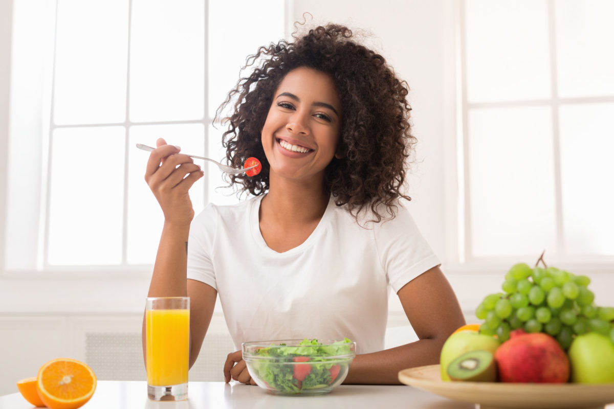 young woman smiles while she enjoys a bowl of fresh greens and a glass of orange juice at a table